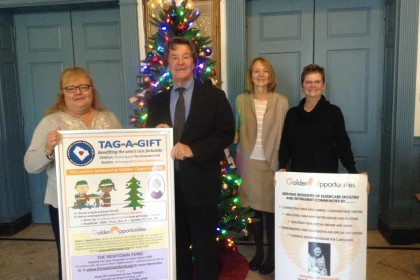 Edmond Town Hall 2015 Giving Tree Sponsors 'Golden Opportunities' of Sandy Hook working with Laura Branchini of the Newtown Junior Women's Club (left) to place gift tags on tree. Left to right, Neil and Susan Callaghan and Knettie Archard, Golden Opportunities founder.