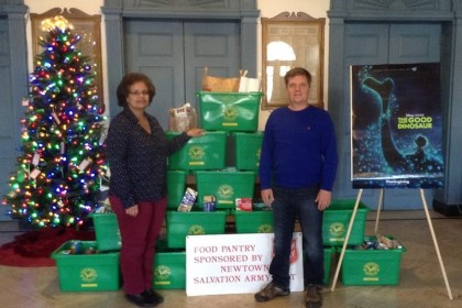 "Andy Clure, recently elected to the Board of Education and founder of the Sandy Hook Arcade Center, stands with Edmond Town Hall Operations Manager Sheila Torres in front of the 17 bins of food donated to the Newtown Food Pantry at a recent preview event of ""The Good Dinosaur"" movie."